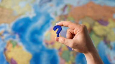 Adult hand holding question mark plastic toy on the world political map background. Travel planning explore destination concept. Quarantine over, borders open