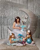 Anya és a lányai várják a karácsonyt. Anya tündérnek öltözött. A lányok a földön ülnek. Az egész család ajándékot ad egymásnak. Boldog szülői életet és gyermekkort. Családi nyaralás.