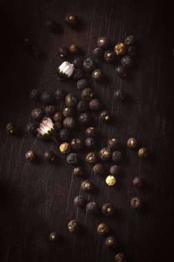 Dry juniper berries spilled on wooden board with daisy blooms