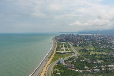 view from the airplane porthole to the resort town of Batumi located in Georgia, on a sunny day with clouds in the sky.