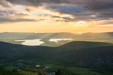 the view of two lakes from the height of the mountain, in the light of the setting sun, the clear cloudless sun. Spring view of the Crimea.