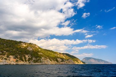 Ayu-Dag mountain from the side of a pleasure boat in the black sea, on a sunny day with clouds in the sky.