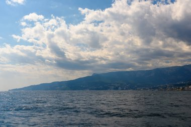 The resort city of Yalta from the side of a pleasure boat in the black sea, on a sunny day with clouds in the sky.