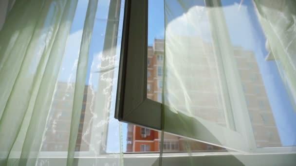 Okno se závěsy a výhled na oblohu a město. Konceptuální příběh pokoje a otevřená okna.