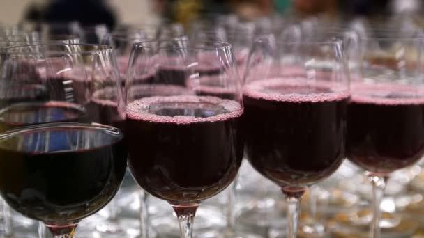 Brýle s alkoholem a různých nápojů, sklenice vína a šťávy jsou na tabulce formou bufetu v restauraci, červené víno v brýlích