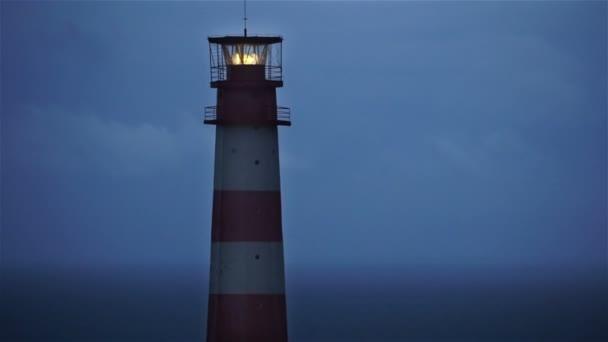 Lighthouse světla spining a okolí. Červený a bílý maják.