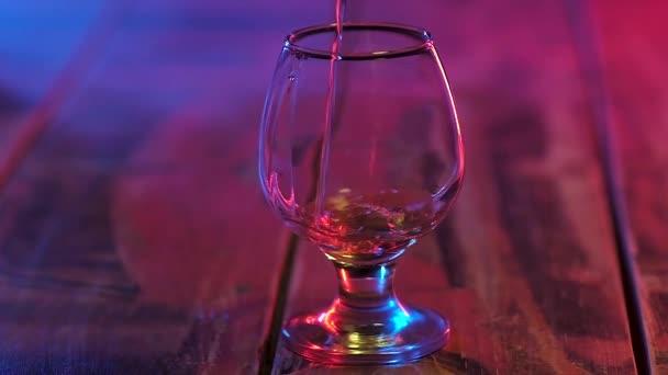 egy átlátszó pohár alkoholtartalmú italok, állva egy fából készült asztal többszínű világítás töltött egy vékony patak a régi erős konyakos. Lassított mozgás.