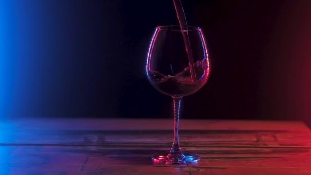 átlátszó üvegben áll egy fából készült asztal töltött vörösbort. Tarka világítás fekete alapon. Lassított mozgás.