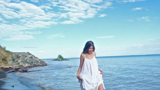 beautiful slender barefoot girl with long dark hair, in a white dress walking on a black sandy beach. twirl and kicks water, creating splashes. Slow traffic on the sea coast in Sunny summer sunset