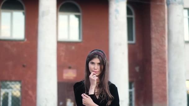 Porträt schöne Mädchen mit langen dunklen Haaren in schwarzem Kleid, mit silbernem Ring am Finger, farbiges Taschentuch auf dem Kopf. Blick auf die Kamera vor dem Hintergrund eines alten roten Gebäudes mit Säulen