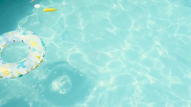 a fiú merülés a vizet játékokkal és egy felfújható kör és úszik a víz alatt. a nézetet felülről. Úszás a saját keret medence egy forró nyári napon. Lassú mozgás, kemény fény.