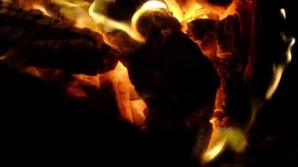 zblízka na večerní oheň s červeným žhavým spálený dřevem v malých plamenech.