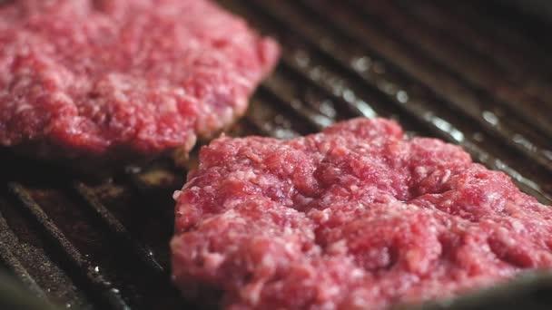 Zwei saftige rohe rote Burger-Patties mit Fettstücken werden auf einer heißen eisernen Grillpfanne mit Antihaftbeschichtung gebraten. in kochendem Olivenöl. Spray und Dampf. Makrofotografie vom Kochen in der heimischen Küche
