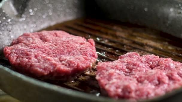 několik čerstvých šťavnatých červených kotlet pro hamburgery se smažou na velké šedé pánvi s nepřilnavou vrstvou v vařící olivovém oleji. hodně sprejů a páry. Panoramatický výroku vaření.