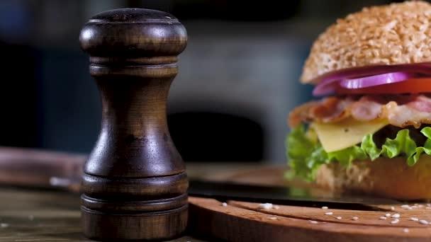 Panoramaaufnahme von Hamburgern mit weichem Sesambrot, gebratenem Schnitzel, Zwiebelringen, Tomate und Käse, knusprigem Speck. Auf dem Tisch liegt ein schwarzer Holzpfefferstreuer, darin liegt ein scharfes Messer. Küche im Hintergrund