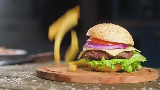 Smažené dlouhé hranolky padají na vařené Burger se salátem, kousek sýra, křupavé slaniny a smažený kotlet ležící na dřevěném tácu. Pomalý pohyb na pozadí kuchyně.