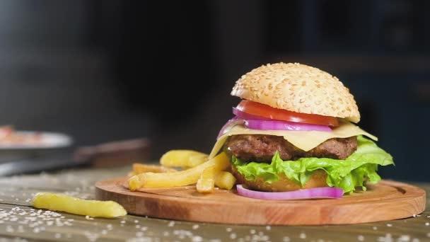 Burger s pikantní smaženou kotlet, kousek sýra a růžových cibulových kroužků leží na dřevěném tácu v pozadí kuchyně. u hranolků