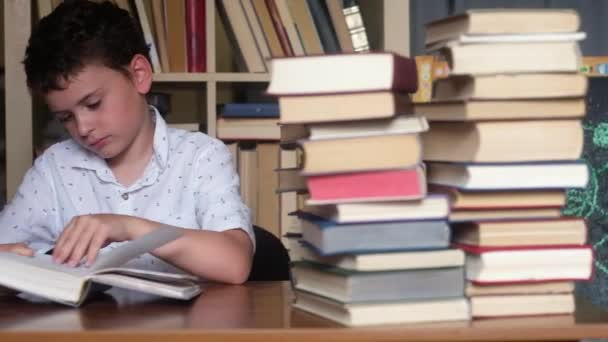 chlapec s tmavými vlasy, s lehkou košilí sedí u stolu a čte si knihu. Chybí. Listování stránkami se opírá o ruku na tváři. spousta knih v hromádce knih. Panoramatické natáčení na pozadí regálu.