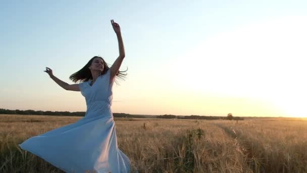 beautiful young girl with long dark hair and blue dress is spinning in wheat field with her arms outstretched. Woman happy. Laughs. Natural light. Against the backdrop of a summer sunset and blue sky.
