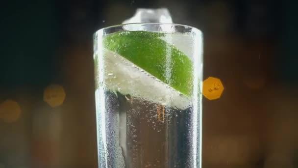 Schier kalte Eiswürfel fallen in das nasse Glas mit sprudelndem Wasser, in dem Kalkscheiben schwimmen. jede Menge Blasen und Spritzer im Getränk. Tropfen fließen auf eine Tasse herunter