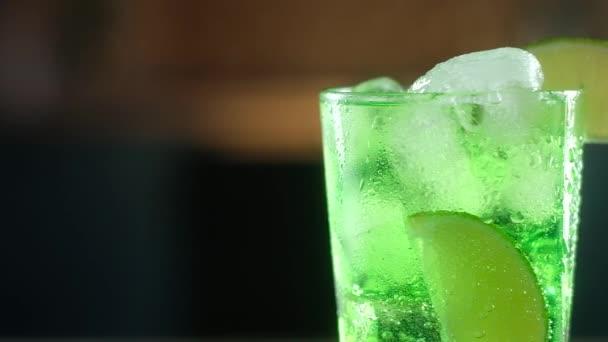 in nassem Glas klares Glas mit Wassertropfen gegossen grünen Cocktail mit großen Würfeln kaltem Eis. Eine Scheibe frischer Kalk wurde auf den Glasrand gelegt. Panorama-Schießen auf festlichen Umtrunk für das neue Jahr