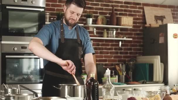 Zubereitung von Lebensmitteln in der heimischen Küche. Ein junger bärtiger Koch in Schürze bereitet in der Küche das Essen zu. Der Koch mischt die Sauce in der Pfanne. Essen in der heimischen Küche. Ein exquisites Gericht für Feinschmecker.