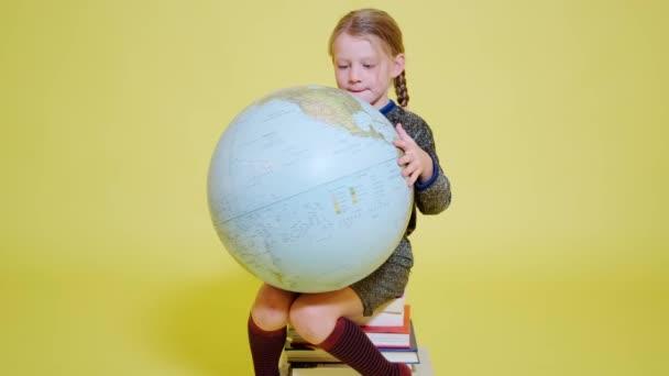 školačka sedící na hromadě knih a studující svět s glóbem