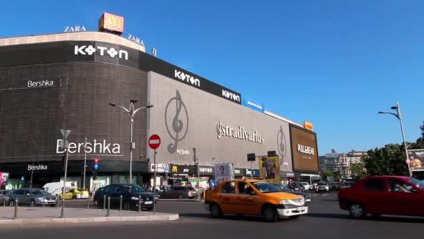 Bucharest, Romania - May 17, 2018: Car traffic near the Bershka and Koton stores located in Unirea Shopping Center, in Unirii Square, Bucharest, Romania.