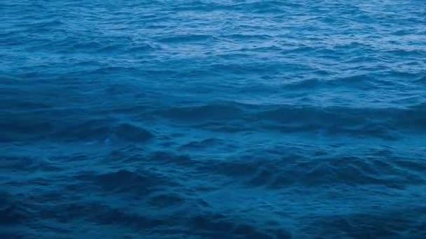 Bohatá modrá Karibská voda, která jede lodí v Karibském moři s vlnami vzdalovat se od člunu