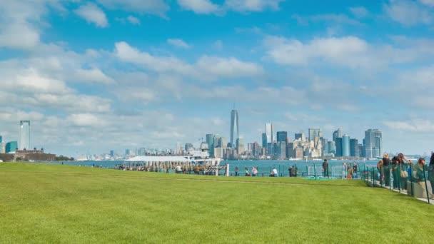 New York City Skyline a Liberty Island-látogatók látogatása és a képek a Szabadság-szobor felvázoló egy zöld fű Lawn egy Sunny Day fehér felhők a Blue Sky