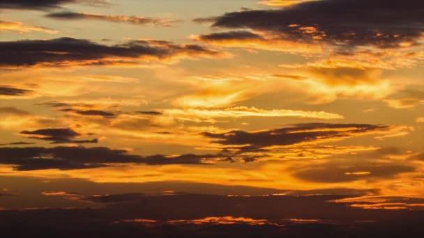 Zlaté barevné Cirrus mraky pohybující se vodorovně během východu nebo západu slunce