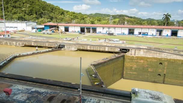 Panamský průplav zavřený s mužem chůze přes vodní zámek, když je voda zadržená před otevřením bran