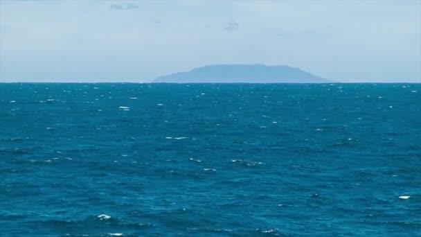 Na moři s pozemním masovým hromaděním na obzoru od lodi procházející modrým oceánem voda za slunečného dne