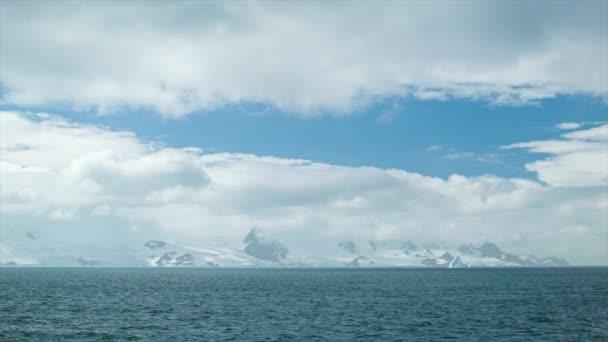 Sunny Antarktida na šířku široký záběr s modrým nebem otevření s ledovci a Moody obláčky