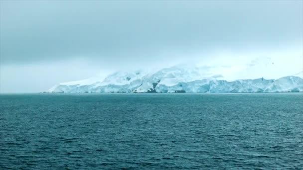 Tekintettel az antarktiszi szárazföldi tömeg egy hajó a Déli-óceán jég és hó fedett rock alatt hideg időjárás