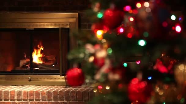 Statická střela požáru v cihlovém krbu s dekorovaným vánočním Stromeštěm v popředí. Zaostřit změny na vánoční stromek.