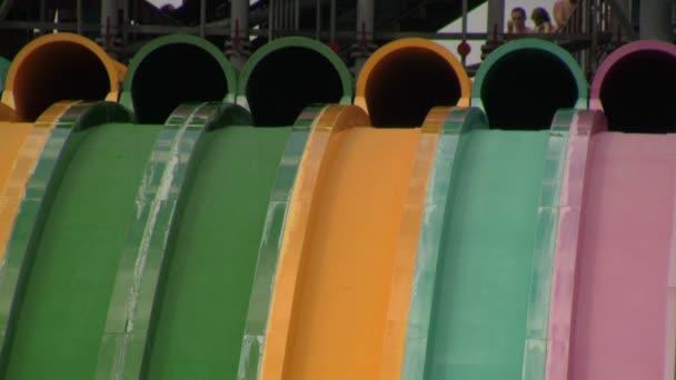 Skupina neznámých mladých lidí, kteří se vynořují z barevných vodovodních skluzavek a závodí dolů do konce řádku na vodním parku Aquatica v Orlandu, Florida.