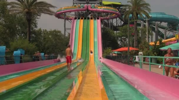 A Group of Unrecognizable Young People Racing Down Multi-colored Speed Slides at Aquatica Water Park in Orlando, Florida.