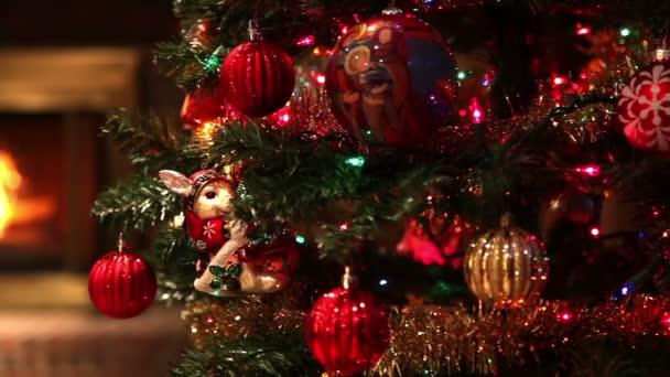 Kamera verfolgt einen Weihnachtsbaum voller Ornamente, der in einem Wohnzimmer steht, und zeigt ein unscharfes Feuer, das im Hintergrund in einem Kamin brennt.