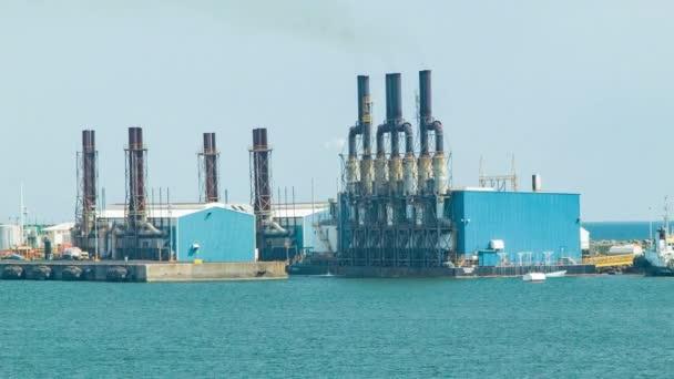 industrielles oceanfront kraftwerk in puerto quetzal guatemala mit rauchabsaugrohren aus einem großen gebäude in der mittelamerikanischen hafenstadt