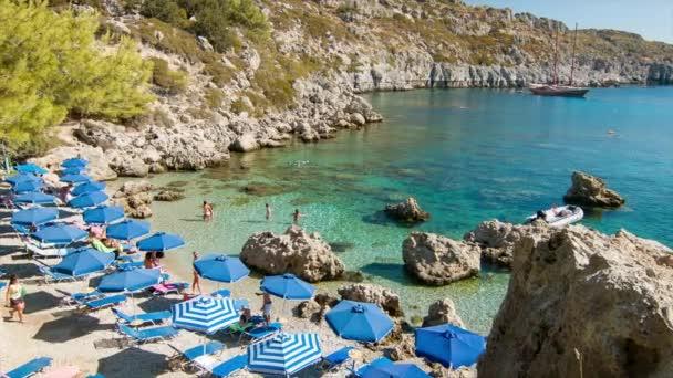 Turisté z Rhodu Řecka užívající Anthony Quinbay s průzračnou modrou mořskou vodou během slunečného dne ve středomořské letní sezóně