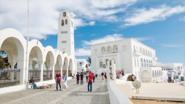 Scéna řecké ulice na Santoríni s turisty vyhlídkami na oblíbený řecký cíl kolem památek a staveb