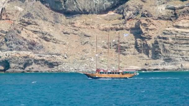 Dřevěné plachetnice na vyhlídkové prohlídce na Santoríni Řecko blízko Středozemního moře s příkrými sopečnými skalními útesy na pozadí