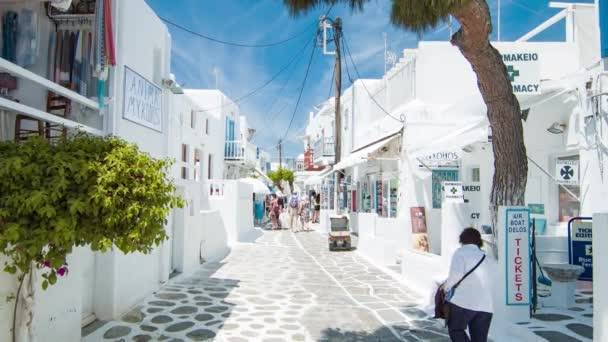 Town Streets of Mykonos Greece in Between White Buildings with Shopping and Sightseeing Tourists Exploring the Popular Summer Mediterranean Travel Destination