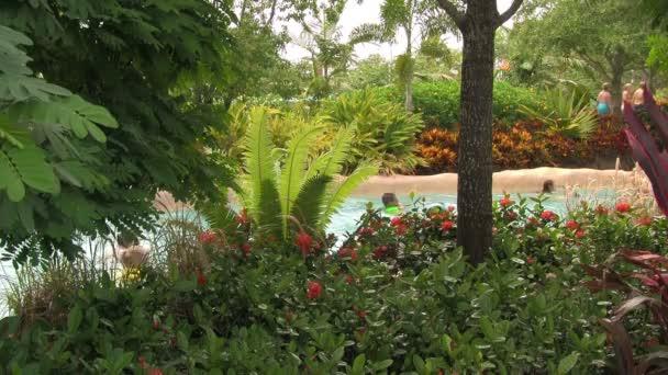 bis zur Unkenntlichkeit treibende Menschen in einem faulen Fluss, der im Sommer in einem üppigen tropischen Garten im Aquatica-Wasserpark von Seaworld in Orlando, Florida, eingebettet ist.