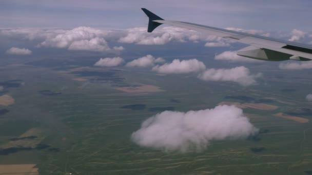 Křídlo letounů na pozadí mraků skrz okno letadla