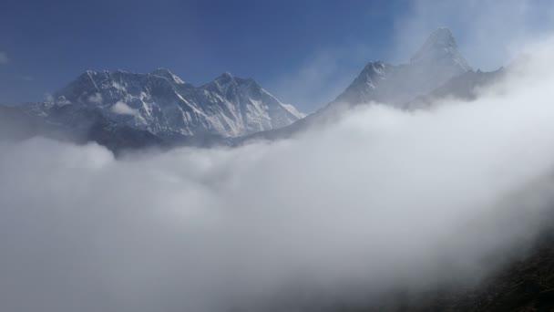 Everest (8848 m), Lhotse (8516 m) a Ama Dablam (6812 m) vrcholy postupně rozpustí do mlhy. Nepál, Himaláje