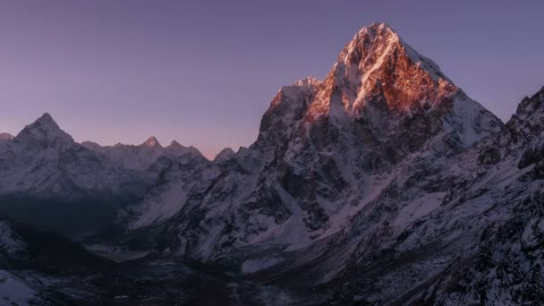 Pohyb slunce na skalní stěně vrcholu Cholatse (6501 m) za východem slunce. Nepál, Himaláje hory. Časová prodleva
