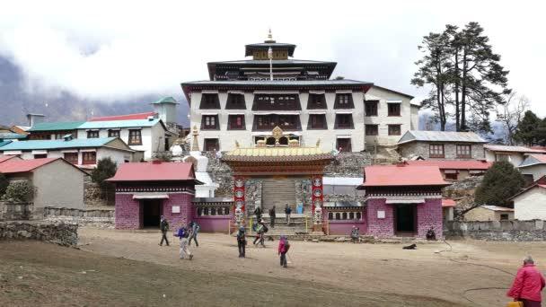 Turisté na cestě do základního tábora vrcholu Everestu na pozadí Tengboche buddhistického kláštera v dubnu, 2018