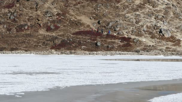 Movement of a group of tourists in the mountains along the shore of a frozen lake with floating duck. Nepal, Himalayas.